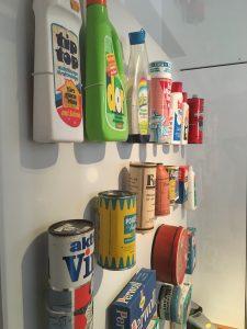 In einer Vitrine sind Verpackungen verschiedener Reinigungsmittel aus unterschiedlichen Zeiten zu sehen