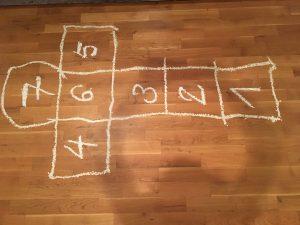 Das Kinderspiel Himmel und Hölle mit weißer Farbe auf de Holzboden lackiert.